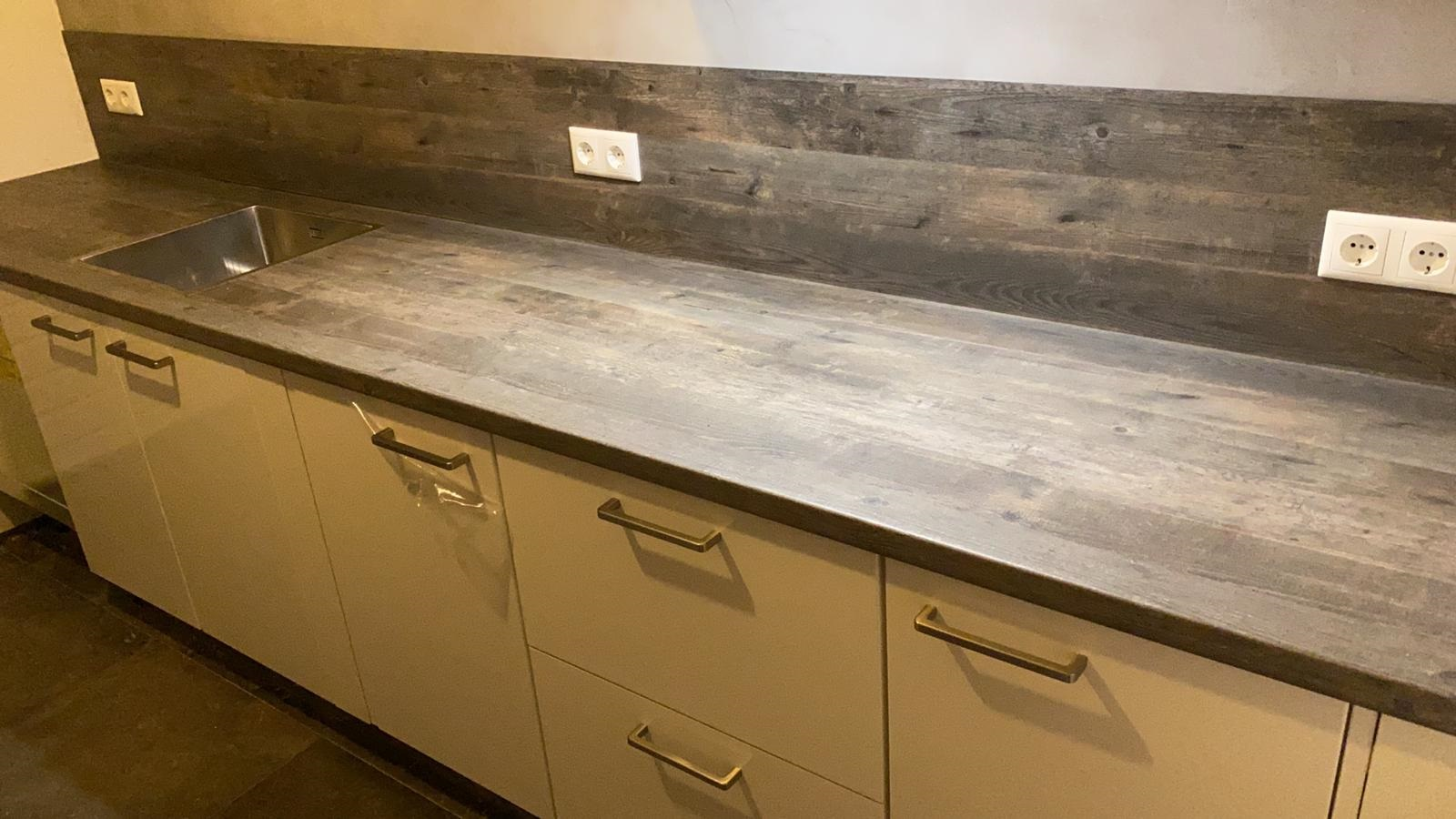 Kunststof hout-look werkblad in keuken. Achterwand in dezelfde kleur. Het materiaal van de achterwand is 4 mm volle kern plaat.